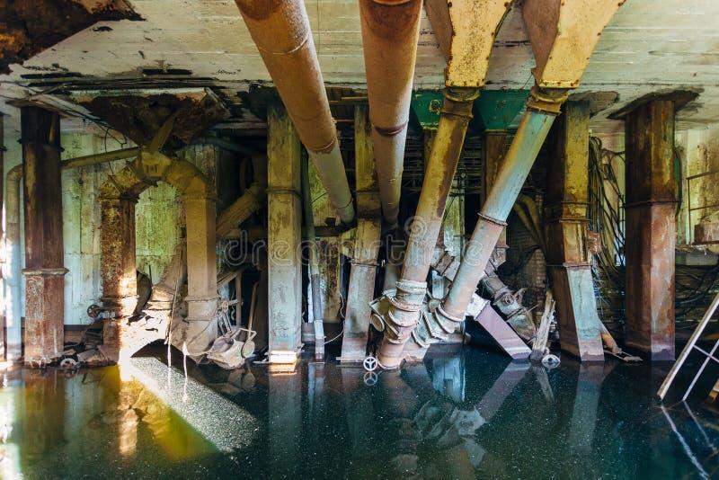 Zalewam porzucał rujnującą fabrykę Stare ośniedziałe drymby w brudnej wodzie obrazy royalty free