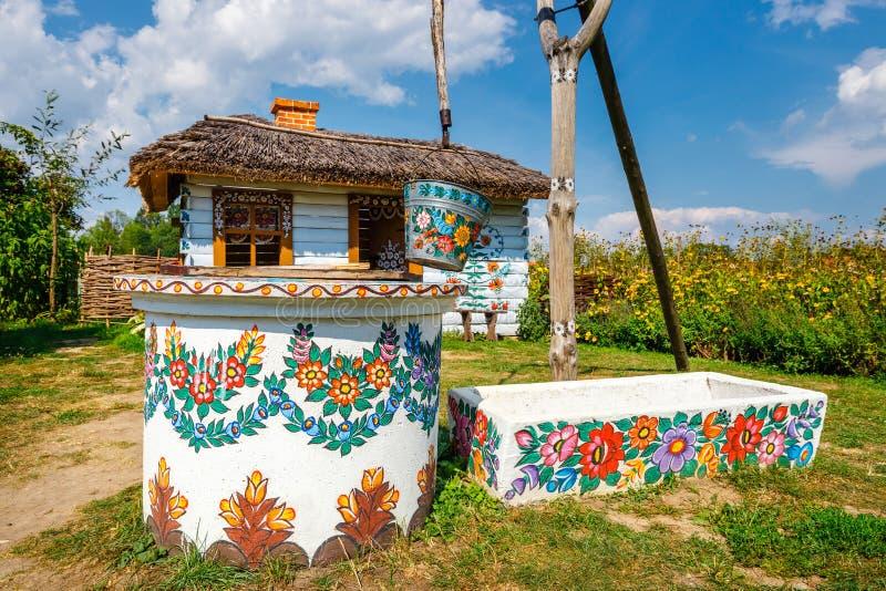 Zalipie, Польша, 19-ое августа 2018: Ведро над хорошо внутри красочная деревня - Zalipie, Польша Знано для местного обычая стоковые фото