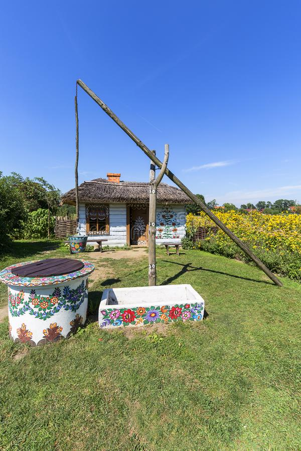 Painted old wooden cottage, well and pail, decorated with a hand painted flowers, Zalipie, Poland royalty free stock photos