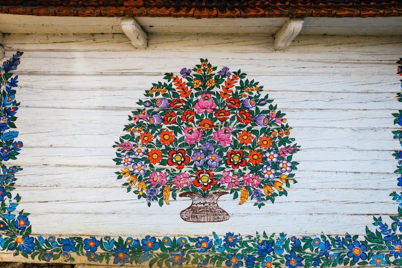 Zalipie, Polonia, el 19 de agosto de 2018: Ciérrese para arriba de las flores coloridas pintadas en la cabaña de madera en Zalipi foto de archivo libre de regalías