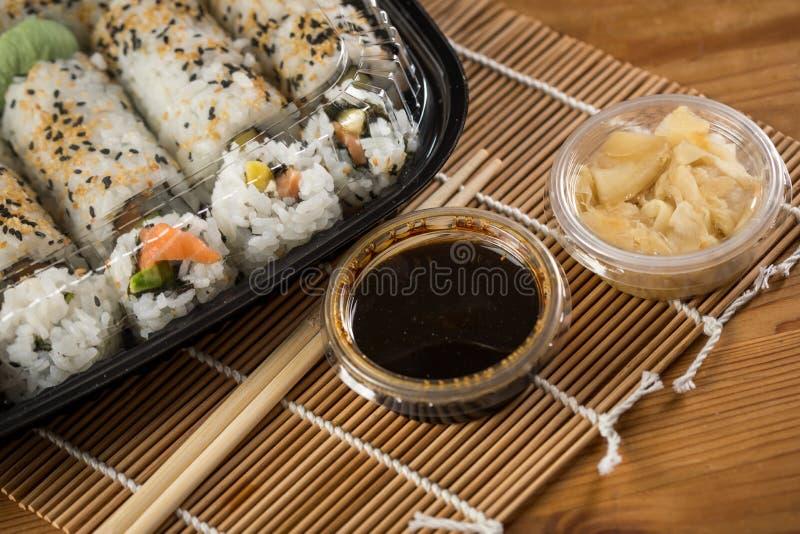 Zalm, avocado en mango binnenstebuiten de sushi van Californi? met sojasaus, legden gember, sojasaus en houten eetstokjes in plas royalty-vrije stock fotografie