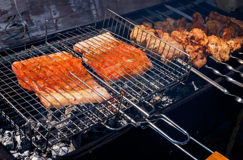Zalm en varkensvleeskebabs die buiten roosteren stock afbeeldingen