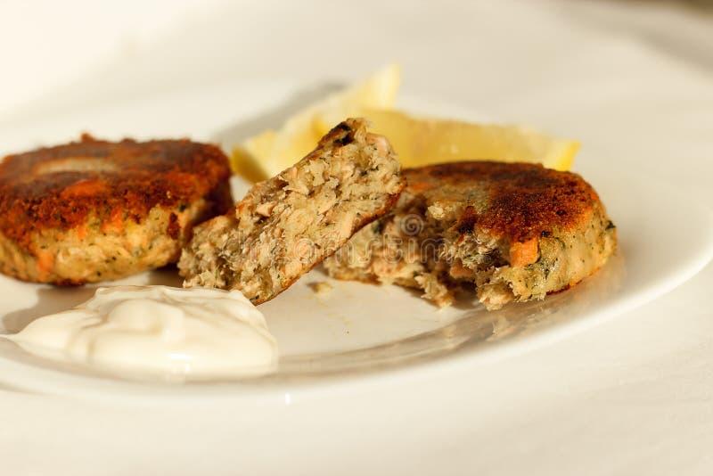 Zalm fishcakes koteletten met witte saus en citroen worden gediend die royalty-vrije stock afbeelding