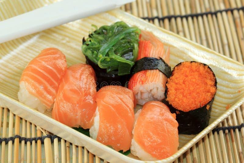 Zalm, garnalen, zeewiersushi in schuimdoos stock afbeeldingen