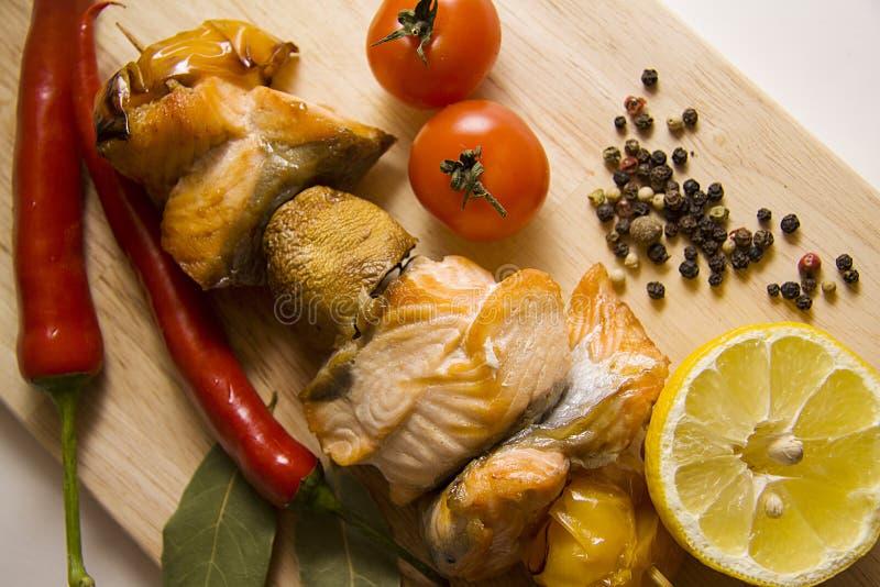 Zalm met Spaanse pepers en tomaten onder contrastbliksem stock fotografie
