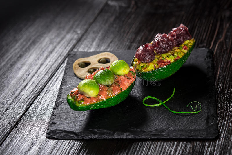 Zalm tartare en avocadosalade op een zwarte achtergrond royalty-vrije stock foto's