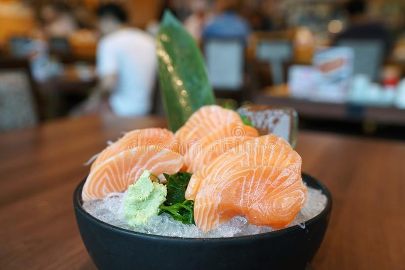 Zalmsashimi - de Ruwe verse gesneden zalm diende op zwarte plaat met wasabi en verscheurde radijs, de eetstokjes van de Handholdi stock foto