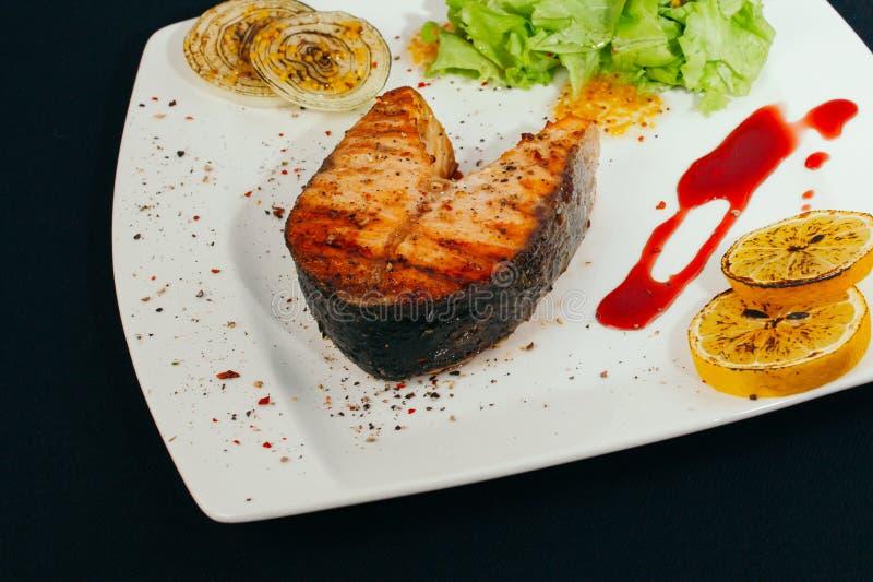 Zalmstaak met rook wordt geroosterd die Het proces van de zalmvoorbereiding bij de grill Geroosterde vissenlapjes vlees op brand  stock foto
