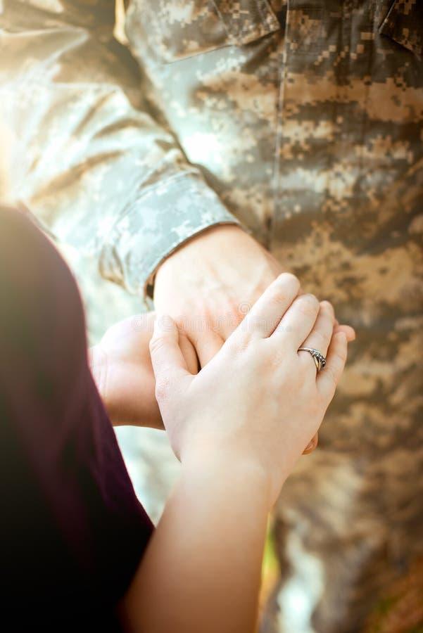 Zamężne militarne pary mienia ręki zdjęcie stock
