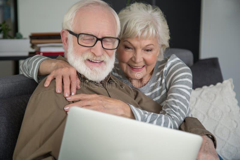 Zamężny dojrzały mąż i żona relaksuje z laptopem zdjęcia royalty free