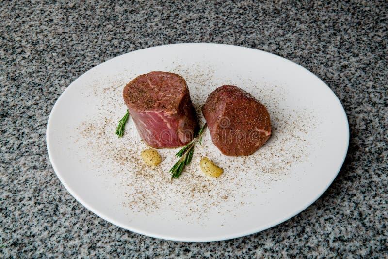 Zamarznięci wołowina stki na białym talerzu zdjęcia royalty free