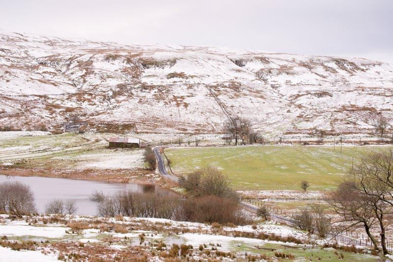 Zamarznięta zimy droga z Lekkim śniegiem na wzgórzach i Loch popieramy kogoś obrazy royalty free