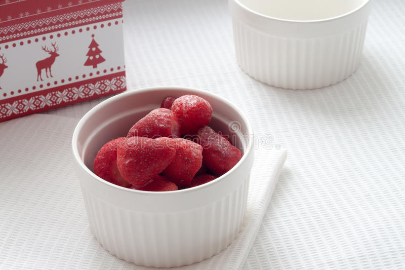 Zamarznięte truskawki w białym talerzu na białym tablecloth blisko Bożenarodzeniowego pudełka fotografia royalty free