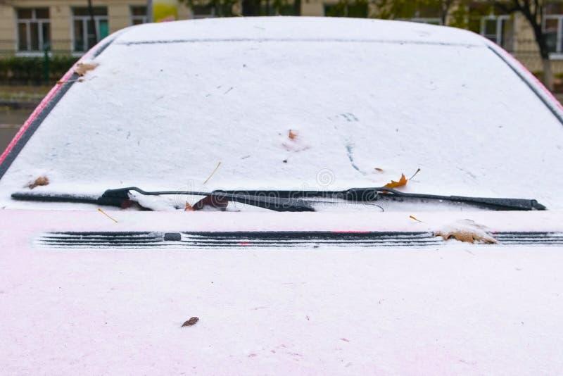 Zamarznięty czerwony samochód zakrywający śnieg przy zima dniem, przegląda frontowego okno przednią szybę i kapiszon fotografia royalty free