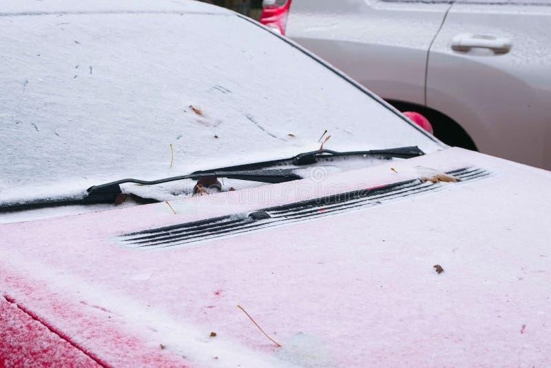 Zamarznięty czerwony samochód zakrywający śnieg przy zima dniem, przegląda frontowego okno przednią szybę i kapiszon obrazy royalty free