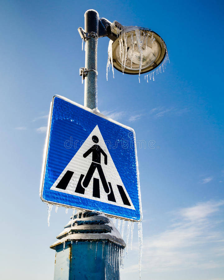 Zamarznięty drogowy znak dla pedestrians z latarnią uliczną above fotografia royalty free