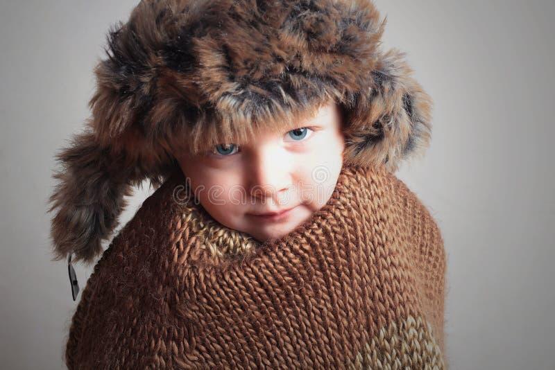 Zamarznięty dziecko w futerkowym kapeluszu mody zimy styl mały chłopiec Dzieci zimno zdjęcia stock