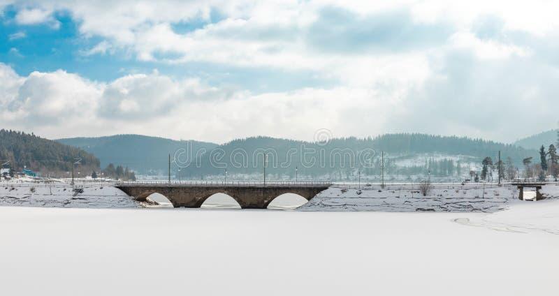 Zamarznięty jeziorny schluchsee z mostem i niebieskim niebem z chmurami w czarnym lesie zdjęcie royalty free