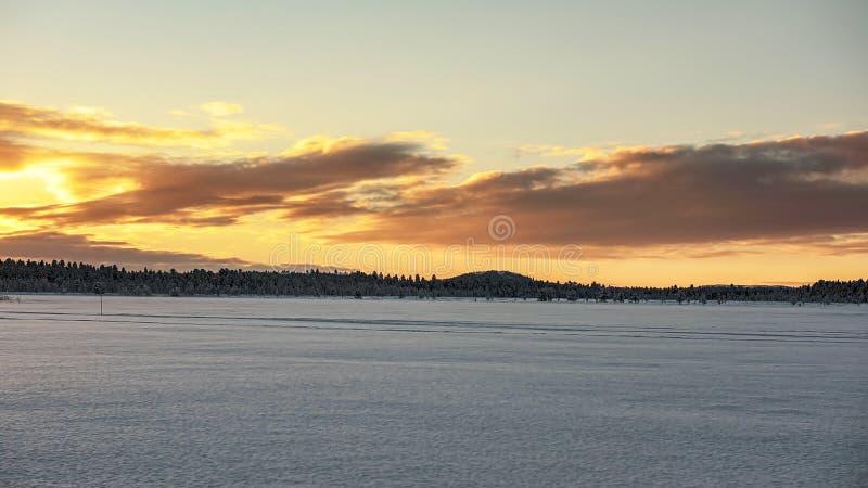 Zamarznięty jezioro pod czerwonym niebem w Lapland zdjęcia stock