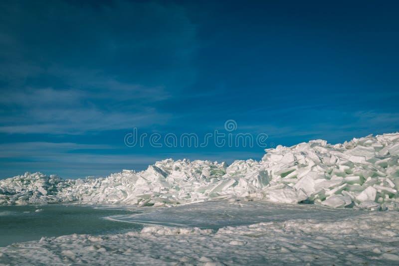 zamarznięty jezioro zakrywający z stertą lodowi floes i niebieskie niebo - vinta fotografia stock