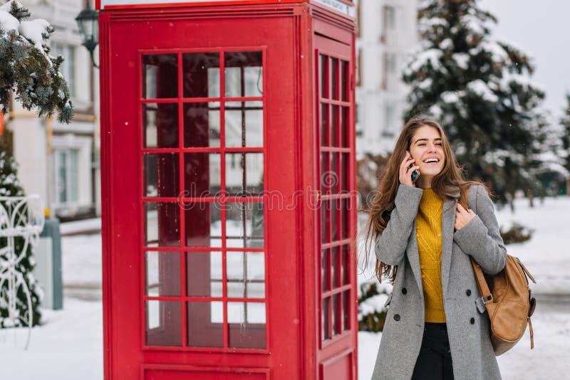Zamarznięty zima czas radosny młody modnej kobiety odprowadzenie na ulicznym pobliskim czerwonym telefonicznym pudełku Opowiada?  fotografia royalty free