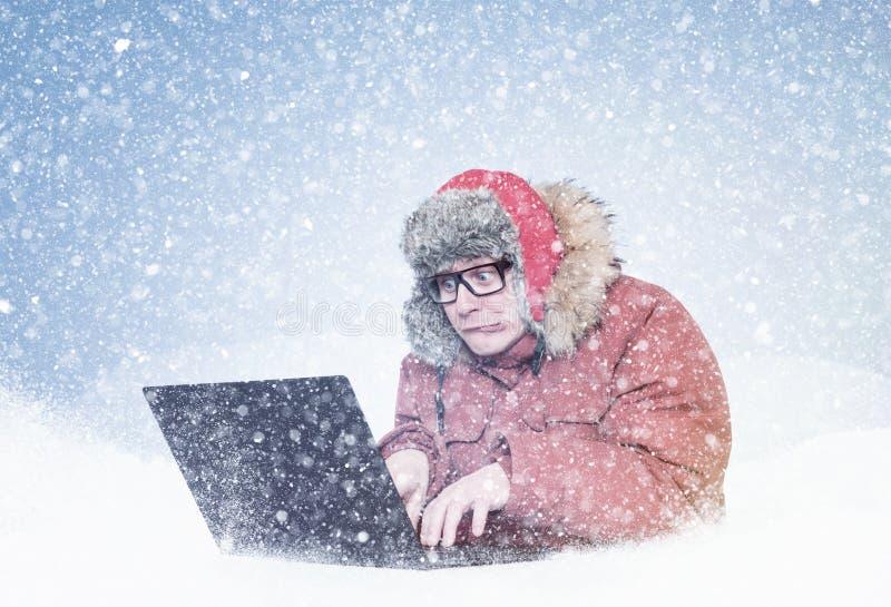 Zamarzni?ty m??czyzna w czerwonej zimy odzie?owym dzia?aniu na laptopie w ?niegu Zimno, mr?z, miecielica obraz royalty free