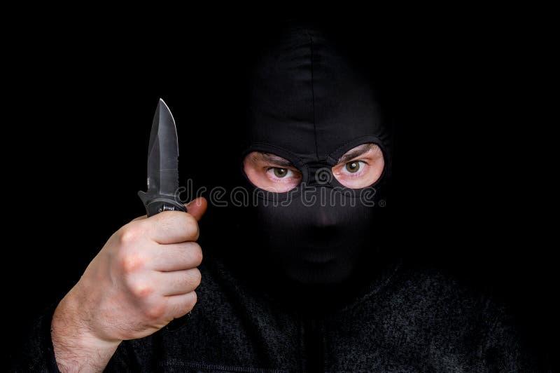 Zamaskowany mężczyzna w balaclava z nożem na czerni fotografia stock