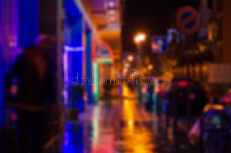 Zamazana fotografia nocy miasta ulica, moczy asfalt, odbicie sklepowi okno obrazy stock