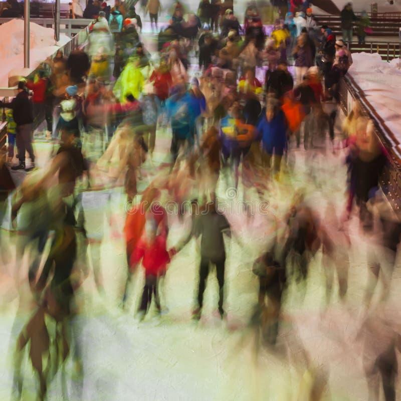Zamazana fotografia wiele persons jeździć na łyżwach na lodowym lodowisku w wieczór czasie outdoors, park na zimie Boże Narodzeni obrazy royalty free