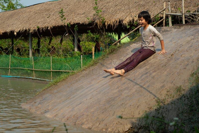 Zamazanego ruchu mokra dziewczyna cieszy się sztuki suwak w borowinowym stawie w gospodarstwie rolnym fotografia royalty free