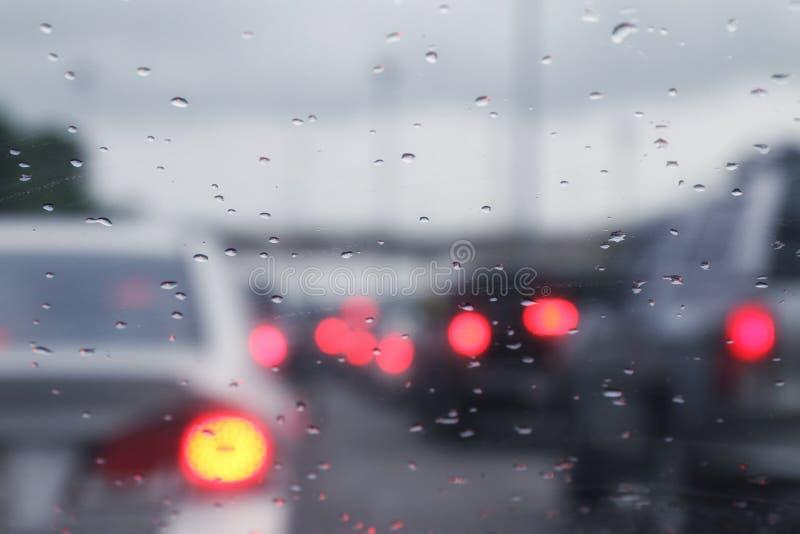 Zamazanego tło ruchu drogowego deszczu i dżemu kropel samochodowa woda na szkle z bokeh oświetleniowym samochodem fotografia stock