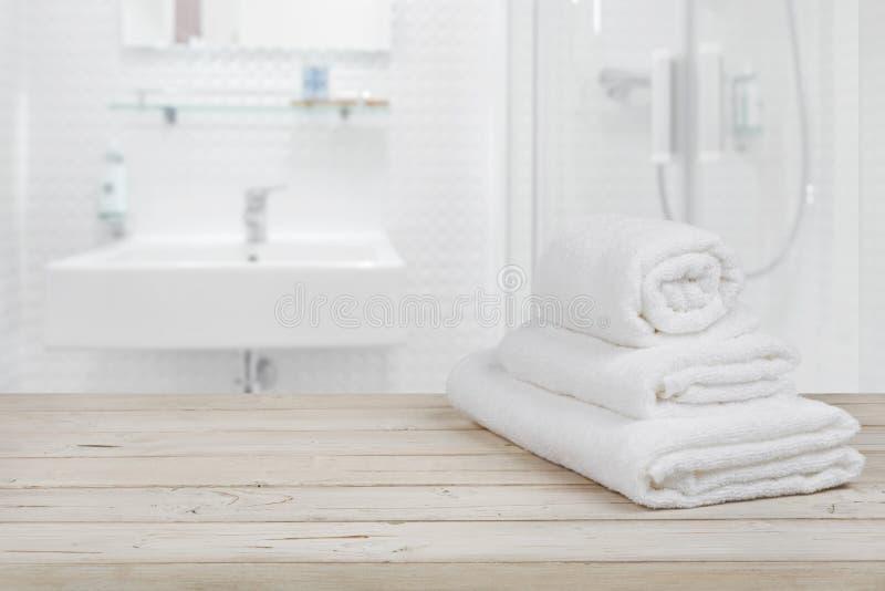 Zamazanej łazienki wewnętrzny tło i biali zdrojów ręczniki na drewnie fotografia stock