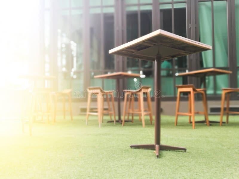 Zamazany drewno stół i krzesło stół na sztucznym zielonej trawy bac zdjęcia royalty free
