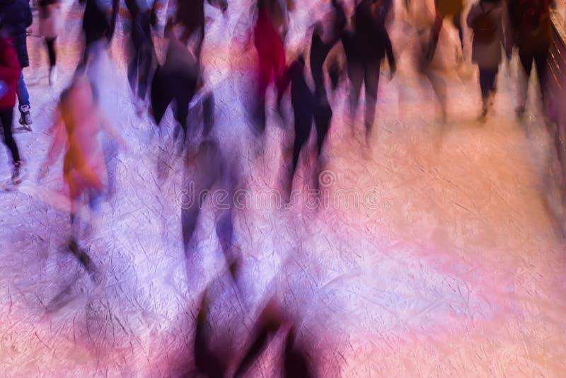 Zamazany lodowy lodowisko z ludźmi w wieczór czasie outdoors, park na zimie Sporta i czasu wolnego pojęcie - jeździć na łyżwach n obrazy stock