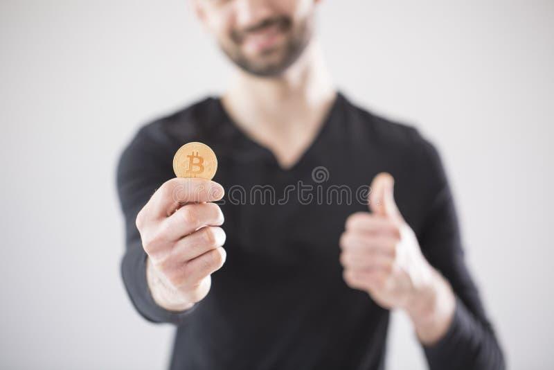 Zamazany mężczyzna trzyma bitcoin i kciuk up w czarnej koszulce obrazy stock