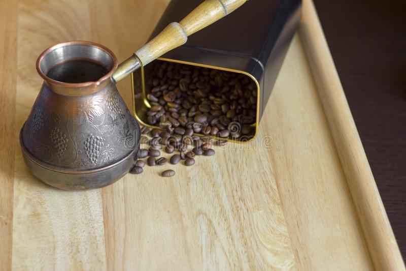 Zamazany rozrzucony brąz piec kawowe fasole od puszki na lekkiej powierzchni stół i miedzianego turka kawowy producent fotografia stock