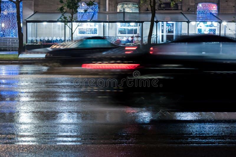Zamazany samochodu jeżdżenia post na mokrej miasto drodze podczas deszczu obrazy royalty free