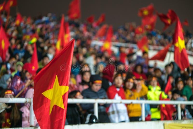 Zamazany tło tłum Wietnamscy fan piłki nożnej przy Mój Dinh stadium Zwolennik podnosi flaga z czerwieni ubraniami obrazy royalty free