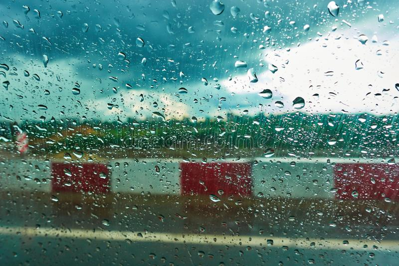 Zamazany tło z deszczem opuszcza na samochodowym szkle jecha? w deszczu zdjęcia royalty free