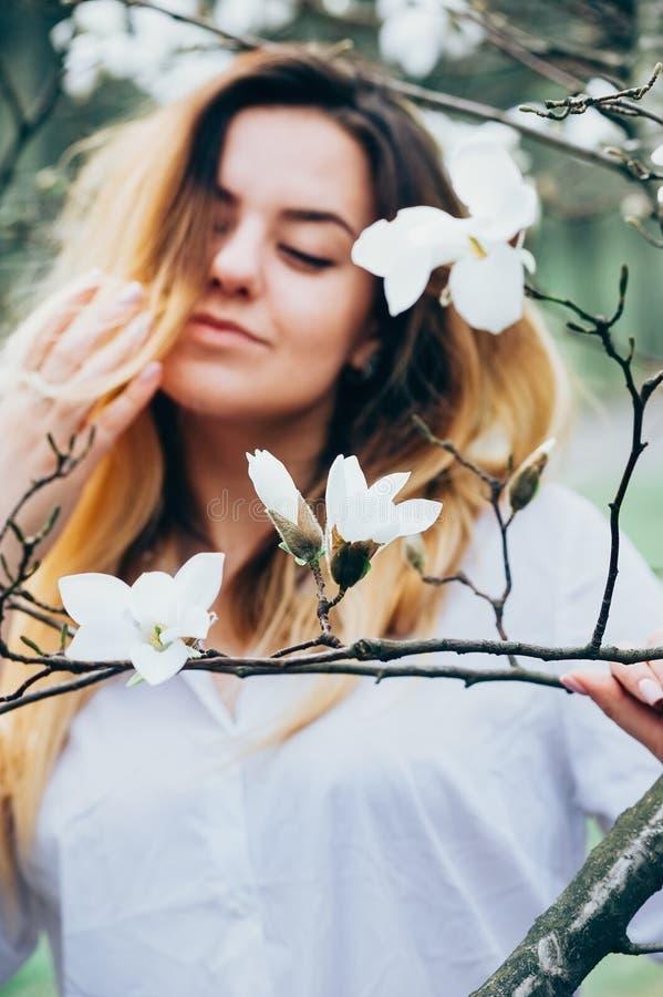 Zamazany wizerunek ładna dziewczyna cieszy się kwitnących magnoliowych drzewa, obraz royalty free