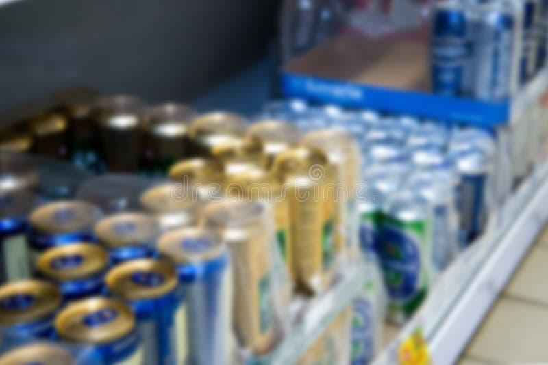 Zamazany wizerunek pakować z konserwować piwem na półce sklepowej obraz stock