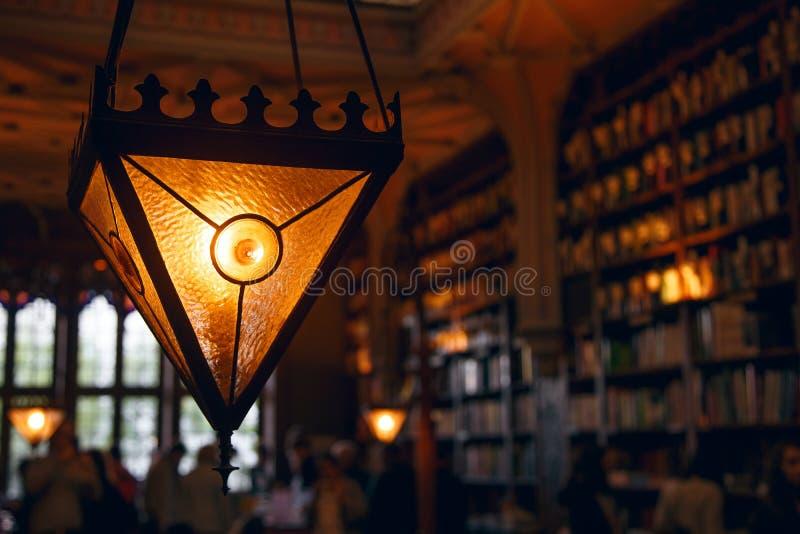 Zamazany wizerunek, wiele stare książki na półce na książki w bibliotece, wielka trójgraniasta lampa obraz royalty free