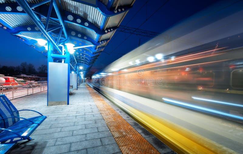 Zamazany wysoki prędkość pociąg na stacji kolejowej przy nocą fotografia stock