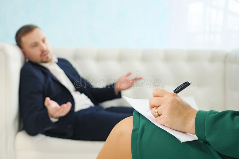 Zamazuj?cy m?ody biznesmena obsiadanie na kanapie opowiada jego terapeuta przy terapii sesj? zdjęcia royalty free