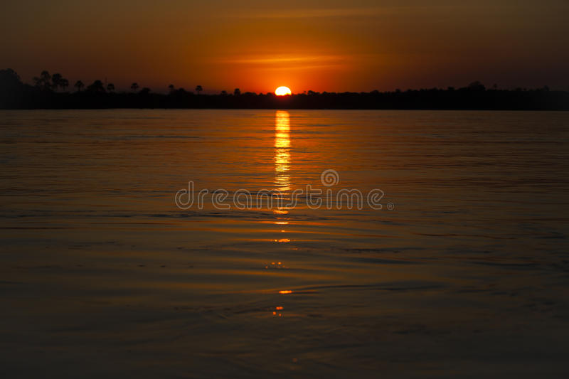 Zambezi River Sunset: Orange Sky and Water. A soft background of palm trees and setting white hot ball of the sun are all that separate the warm, deep, orange stock images