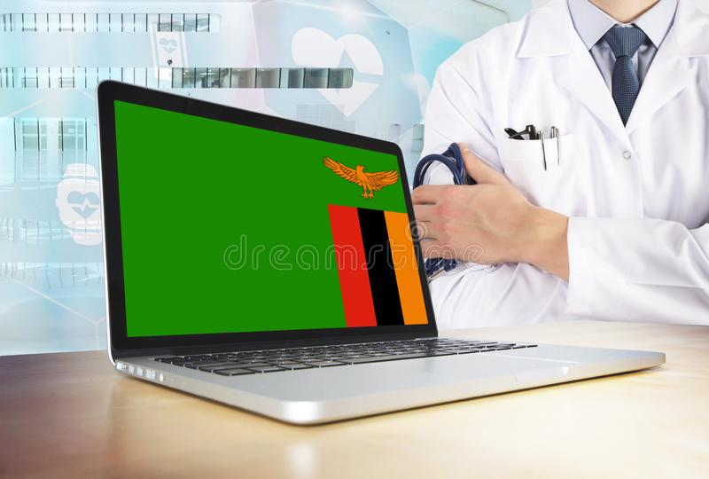 Zambia healthcare system in tech theme. Zambian flag on computer screen. Doctor standing with stethoscope in hospital. stock images