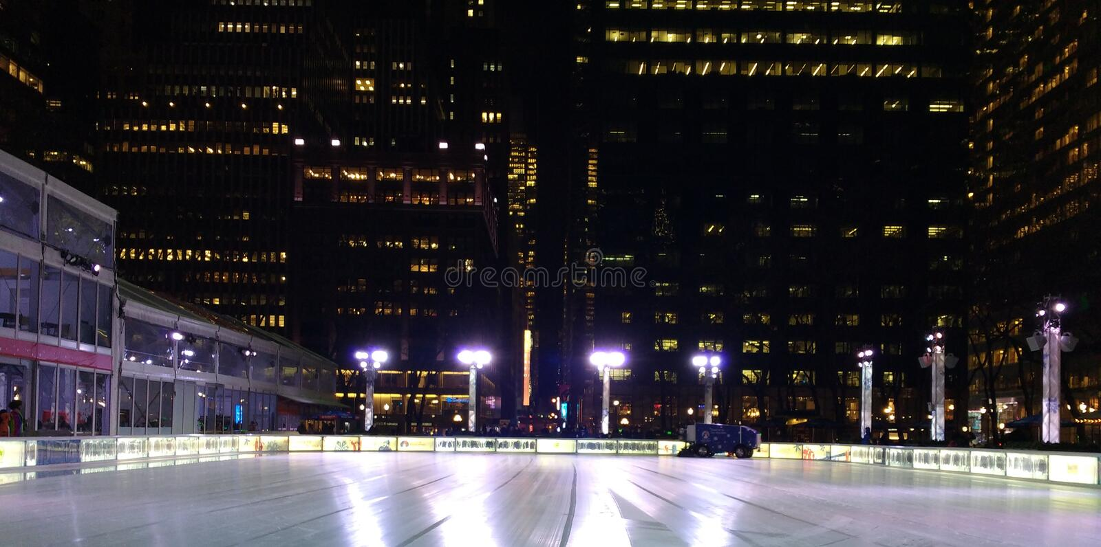 Zamboni reblanchissant la piste de patinage de glace au village d'hiver chez Bryant Park, horizon de New York City la nuit, NYC,  photographie stock libre de droits
