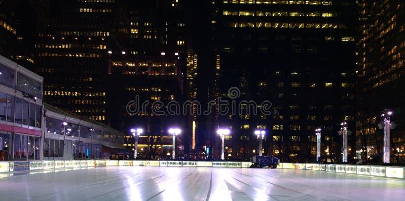 Zamboni, welches die Eislauf-Eisbahn am Winter-Dorf bei Bryant Park, New- York Cityskyline nachts, NYC, NY, USA erneuert lizenzfreie stockfotografie