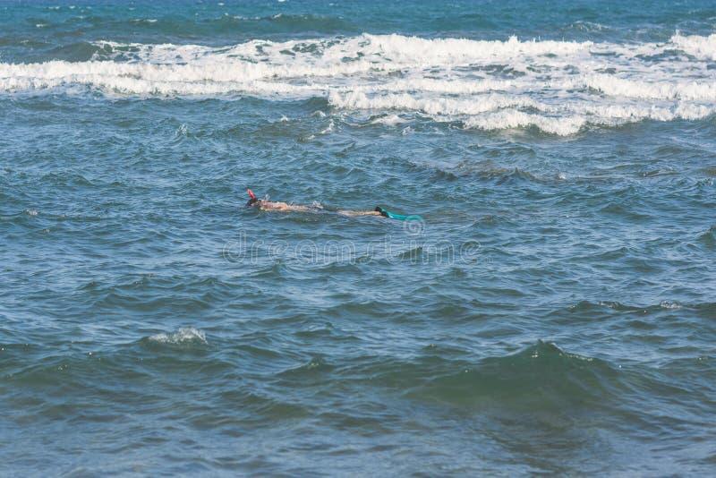 Zambullidas del hombre en la máscara y el tubo que bucean de las aletas que nadan en las ondas de la tormenta foto de archivo