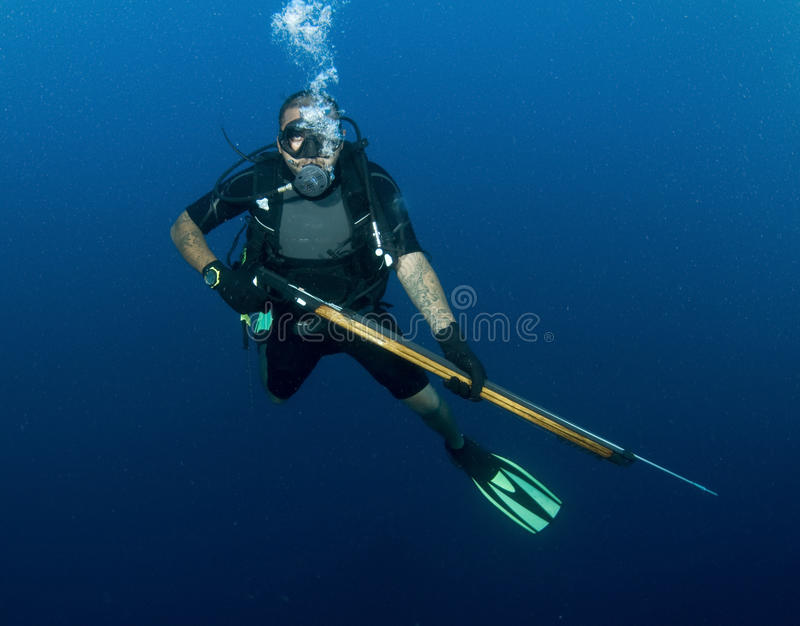 Zambullidor de equipo de submarinismo con el arma de lanza foto de archivo